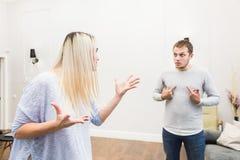 Unglückliche junge Paare, die im Wohnzimmer streiten stockfotos