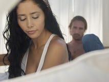 Unglückliche junge Paare im Bett Stockfotos