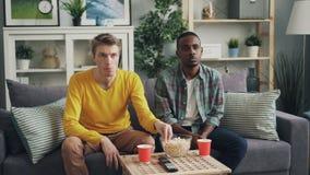 Unglückliche Kerle der jungen Leute, die mit umgekippten Gesichtern fernsehen und das Popcorn zu Hause sitzt auf Couch zusammen e stock footage