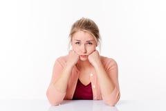 Unglückliche nette junge blonde Frau, die, schauend traurig und schmollt kindisch Lizenzfreie Stockfotografie