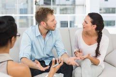 Unglückliche Paare, die an der Therapie-Sitzung argumentieren Lizenzfreies Stockbild