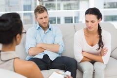 Unglückliche Paare mit den Armen gekreuzt an der Therapie-Sitzung Stockbilder