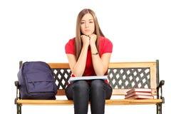 Unglückliche Studentin, die auf einer Holzbank sitzt Stockbilder