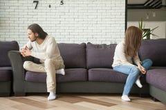 Unglückliche traurige Paare, die zu Hause auf Couch nach Streit sitzen stockfotografie