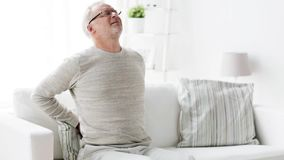 Unglücklicher älterer Mann, der zu Hause unter Rückenschmerzen 134 leidet stock video