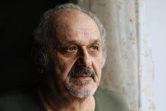 Unglücklicher alter Mann zuhause: älterer Mann mit grauer Bart- und Schnurrbartstellung nahe Fenster Einsamkeit, gealtertes Leute stockfotos