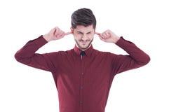 Unglücklicher, betonter Mann, der seine Ohren bedeckt und seine Augen schließt Lizenzfreies Stockfoto