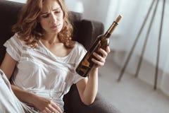 Unglücklicher Brunette, der die emotionalen Schmerz mit Alkohol entlastet Lizenzfreie Stockfotografie