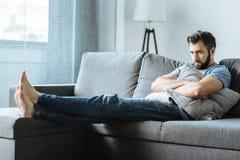 Unglücklicher deprimierter Mann, der ein Kissen hält Stockfoto