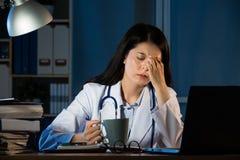Unglücklicher Doktor mit den Kopfschmerzen betont, Kaffee halten stockfoto