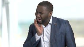 Unglücklicher dunkelhäutiger Geschäftsmann, der unter Zahnschmerzen leidet stock video footage