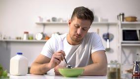 Unglücklicher einsamer Mann, der mit Ekel Nahrung in der Schüssel, Mangel an Appetit betrachtet stockbild