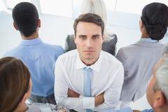 Unglücklicher Geschäftsmann, der Kamera mit seinem Kollegen um ihn betrachtet Lizenzfreie Stockfotos