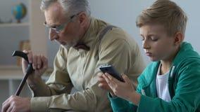 Unglücklicher Großvater, der Enkelblättern Smartphone, Mangel an Kommunikation betrachtet stock video