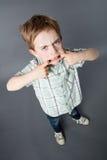 Unglücklicher Junge, der mit großem Mund für entschlossene Haltung steht Stockbilder