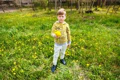 Unglücklicher Junge mit einem Blumenstrauß des Löwenzahns stockbild