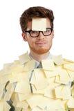 Unglücklicher junger Mann mit einer klebrigen Anmerkung über sein Gesicht, abgedeckt mit Aufklebern Lizenzfreie Stockfotos