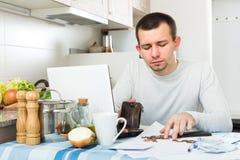 Unglücklicher Kerl mit Notizbuch an der Küche Lizenzfreies Stockbild