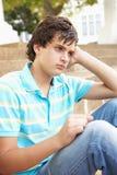 Unglücklicher männlicher Jugendkursteilnehmer, der draußen sitzt Stockfotografie