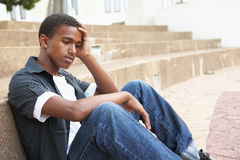 Unglücklicher männlicher Jugendkursteilnehmer, der draußen sitzt Stockfotos