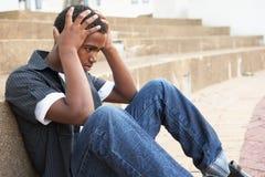 Unglücklicher männlicher Jugendkursteilnehmer, der draußen sitzt stockfoto