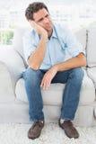Unglücklicher Mann, der auf der Couch weg schaut sitzt Lizenzfreie Stockfotografie