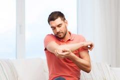 Unglücklicher Mann, der in der Hand unter den Schmerz zu Hause leidet Stockbilder