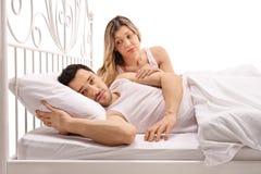 Unglücklicher Mann, der im Bett mit der beteiligten Frau tröstet ihn liegt Stockbilder