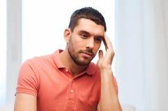 Unglücklicher Mann, der zu Hause unter Kopfschmerzen leidet Lizenzfreies Stockbild