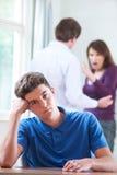 Unglücklicher Teenager mit den Eltern, die im Hintergrund argumentieren stockfotografie