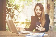 Unglücklicher Unternehmer, der mit einem Telefon und einem Laptop in einem Kaffee arbeitet stockbild