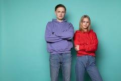 Unglücklicher verärgerter Leutemann und -frau in der zufälligen Kleidung, zusammen stehend gegen blaue Wand im Studio lizenzfreies stockfoto