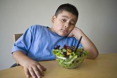 Unglücklicher vorjugendlicher Junge, der am Schreibtisch mit Salat sitzt lizenzfreie stockfotos
