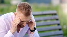 Unglücklicher zufälliger Mann, der die Kopfschmerzen massieren den Tempel sitzt auf Bank an der mittleren Nahaufnahme des Sommerp stock video