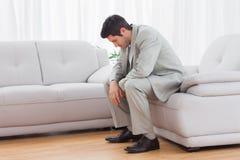 Unglückliches buinessman, das auf dem Sofa senkt seinen Kopf sitzt Lizenzfreies Stockbild