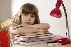 Unglückliches kleines Mädchen, das am Schreibtisch sitzt Stockbilder