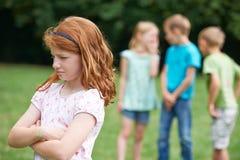 Unglückliches Mädchen, das ungefähr von anderen Kindern geklatscht wird lizenzfreies stockbild