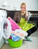 Unglückliches Mädchen, das Waschmaschine verwendet Stockbild