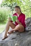 Unglückliches Mädchen 20s, das ein Sommerbuch unter einem Baum liest Lizenzfreies Stockbild