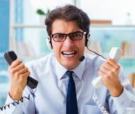 Ungl?ckliche ver?rgerte Call-Center-Arbeitskraft frustriert mit Arbeitsbelastung stockfotografie