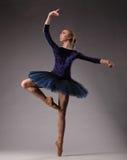 Unglaublich schöne Ballerina in der blauen Ausstattung wirft im Studio auf Kunst des klassischen Balletts Lizenzfreie Stockfotos
