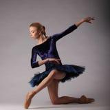 Unglaublich schöne Ballerina mit perfektem Körper in der blauen Ausstattung, die im Studio aufwirft Kunst des klassischen Ballett Stockfoto