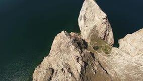 Unglaubliche Luftbrummenansicht der Spitze 4k über enorme Steinfelsengebirgsklippe in Meerblick der Baikalsee-Ruhewasser Russland stock footage