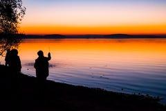 Unglaublicher, heller Sonnenuntergang über dem Wasser stockfotografie