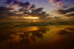 Unglaublicher Sonnenuntergang mit Wolken reflektierte sich im nassen Sand auf Strand Stockfotografie
