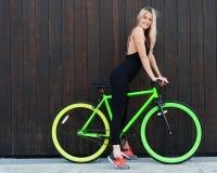 Unglaubliches athletisches blondes Mädchen in der schwarzen sexy Ausstattung mit dem reizend Lächeln, das mit grünem hellem örtli Stockbild