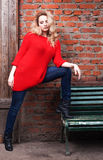 Unglaubliches blondes Mädchen, das in der modischen roten Strickjacke, in den Jeans und in den schwarzen Stiefeln aufwirft Lizenzfreies Stockbild