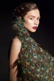 Unglaubliches Modeschönheitsporträt des attraktiven Mädchenmodells mit Pfau versieht mit Federn Lizenzfreie Stockfotografie