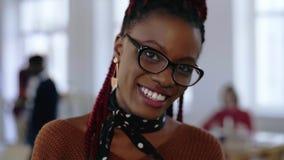 Unglaubliches Nahaufnahmeporträt der jungen glücklichen afrikanischen kreativen Geschäftsfrau in den intelligenten Brillen lächel stock footage