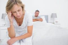 Unglückliche Paare, die an den anderen Enden des Betts nach einem Kampf sitzen Stockfotografie